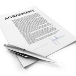"Signed document titled ""Agreemen"" laying on white reflective background."